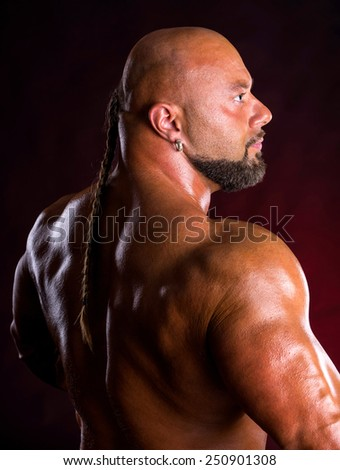 Athlete bodybuilder  demonstrating muscles of the back and arms on a dark red background - stock photo