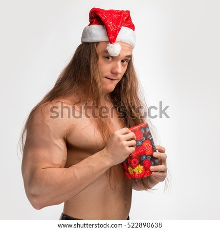 athlete bodybuilder shirtless with long hair posing in cap Santa Claus with a gift in hand on white background