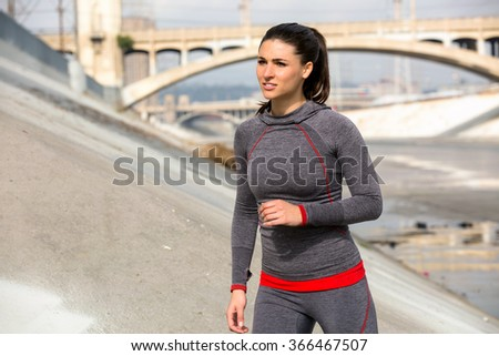Athlete brunette woman jogger running in city urban background with bridge