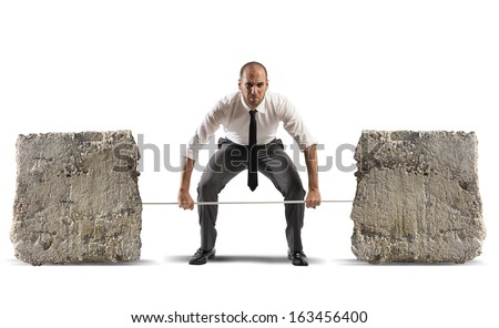 Athlete business man with barbell and heavy stones - stock photo
