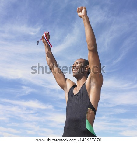 Athlete cheering while holding medal