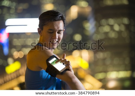 Athlete Chinese man outdoors, using his smart phone in urban city at night. Male fitness concept. - stock photo