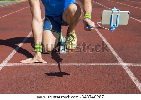 Athlete crouching at the starting line of a running track taking selfie with his mobile phone on a selfie stick. Focus on smartphone