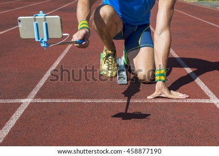 Athlete crouching at the starting line of a running track taking selfie with his mobile phone on a selfie stick