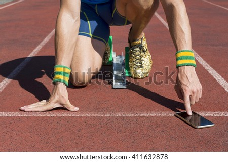 Athlete crouching at the starting line of a running track wearing Brazil colors wristbands checking his mobile phone - stock photo