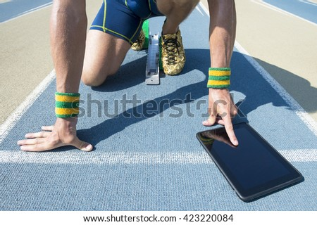 Athlete crouching at the starting line of a running track wearing Brazil colors wristbands using his tablet