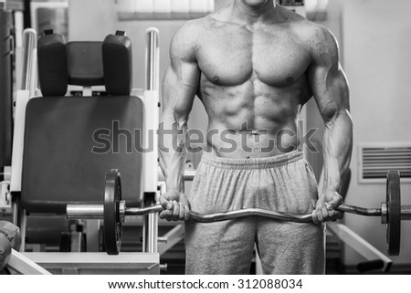 Athlete demonstrates muscles in the gym. Muscle tension of exercise performed. Weight training. Bench weights and work with dumbbells.  - stock photo