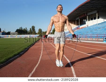Athlete doing exercize at the stadium - stock photo