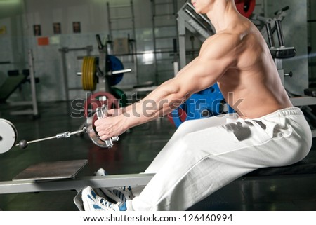athlete doing fitness training on machine with weights in a gym - stock photo