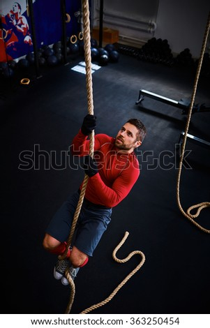 Athlete doing rope climb at gym - stock photo