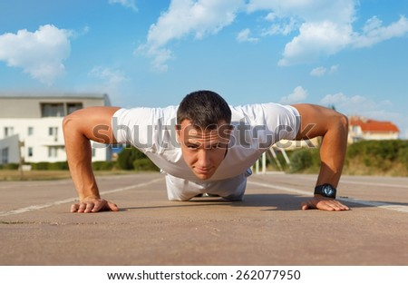 Athlete doing squeezing at the stadium - stock photo
