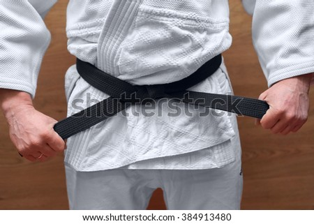 athlete dressed in a kimono with a black belt