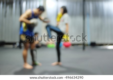 Athlete exercising and fighting. Young girl doing boxing training with coach in gym. Martial arts and self defense.