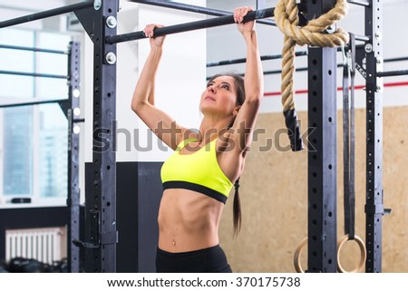 Athlete fit woman performing pull ups in a bar exercising at gym. - stock photo
