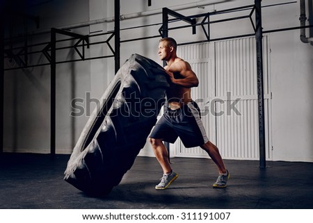 Athlete flipping tire at gym
