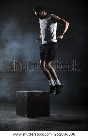 Athlete gave exercise. Jumping on the box. Phase touchdown. Studio shots in the dark tone. slight motion blur - stock photo