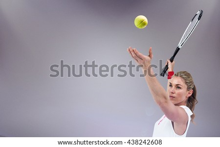 Athlete holding a tennis racquet ready to serve against grey background - stock photo