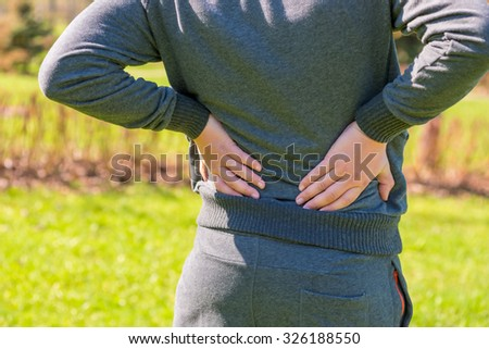 Athlete holding hands sore lower back - stock photo