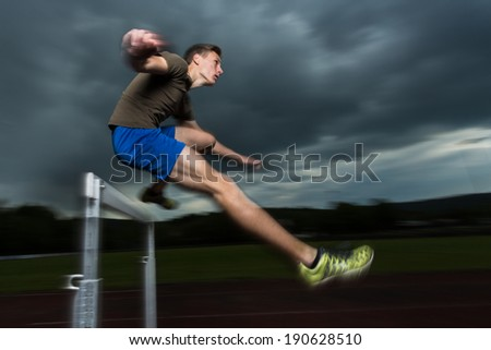 athlete hurdling in track and field - stock photo