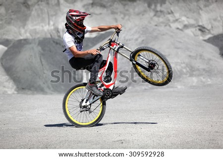 Athlete in a helmet riding a mountain bike on the back wheel in extreme style trial - stock photo