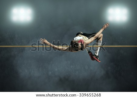 Athlete in action of high jump. - stock photo