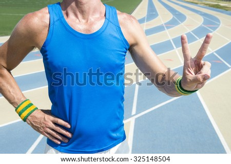 Athlete in Brazil colored wristbands holding up peace sign victory fingers at the running track