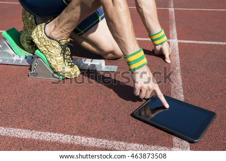 Athlete in gold running shoes crouching at the starting line of a running track wearing Brazil colors wristbands using his tablet