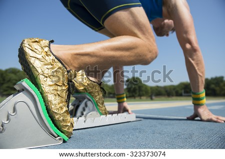 Athlete in gold shoes starting a race from the starting blocks on a blue running track  - stock photo