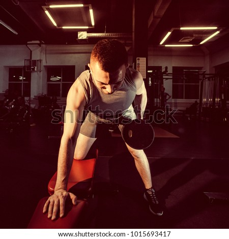Athlete in the gym training with dumbbells. Toned image. Man engaged in fitness. Young man is engaged with dumbbells on the bench