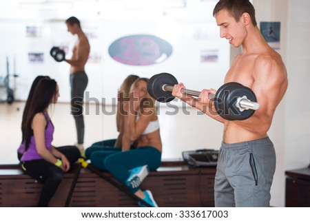 Athlete in the gym training with girls