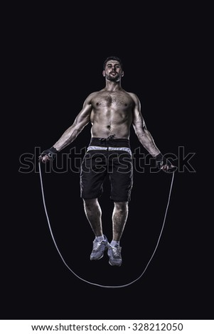 Athlete jumping on skipping rope isolated on black background - stock photo