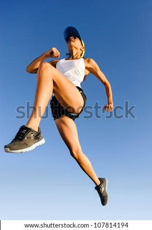 Athlete jumping shot from low angle with sky background - stock photo