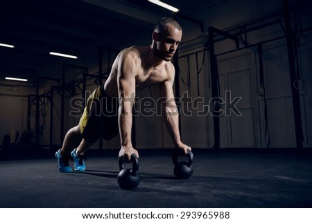 Athlete making push ups on kettlebells for better strength and stability - stock photo