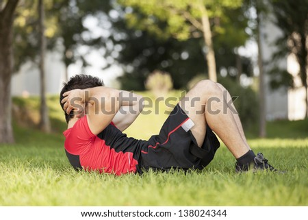 Athlete male at the city park making some abdominal - stock photo