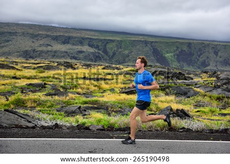 Athlete male runner running on mountain road. Running man jogging fast training cardio for marathon on countryside path in nature landscape, volcano background. Young Caucasian adult in his 20s. - stock photo