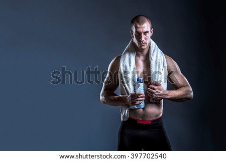 athlete man bodybuilder with towel and water after gym on dark background with copy space - stock photo