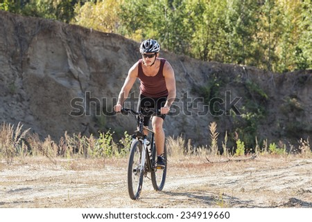 athlete man cycling on a bicycle ounddors in stone pit - stock photo