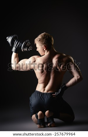 Athlete man doing exercises with dumbbells. Bodybuilding. Muscles of the arms and back. Studio shot over black background. - stock photo