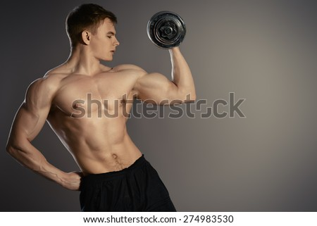 Athlete man doing exercises with dumbbells. Bodybuilding. Muscles of the arms. Studio shot. - stock photo