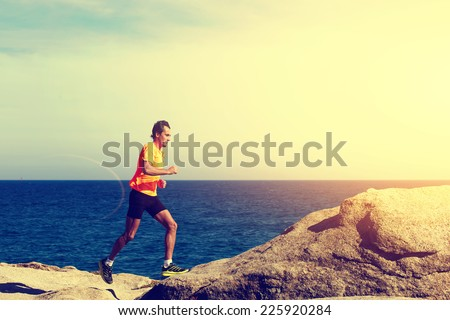 Athlete man in bright fluorescent t-short running fast along the sea at sunset - stock photo