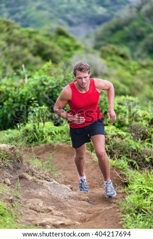 Athlete man runner trail running on mountain nature path outdoors. Athletic young man jogger training hard jumping going up on cross country race uphill outdoors. Energy and endurance concept. - stock photo