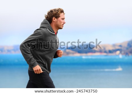 Athlete man running in sweatshirt hoodie in autumn fall by the water. Male runner training outdoors jogging in nature. - stock photo