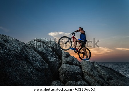 Athlete man with a bike on the rock during sunset - stock photo