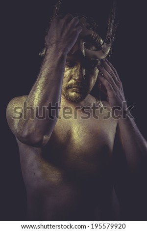 Athlete man with body painted gold feather mask and steel sword - stock photo