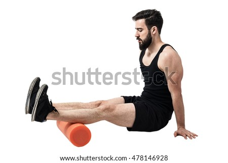Athlete massaging and stretching hamstring leg muscles on foam roller. Full body length portrait isolated on white studio background.