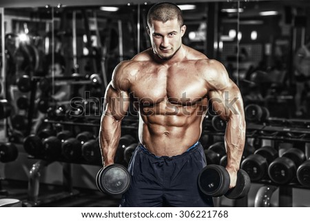 Athlete muscular bodybuilder man demonstrates his muscles in the gym - stock photo