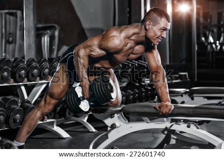 Athlete muscular bodybuilder training back with dumbbell  in the gym - stock photo