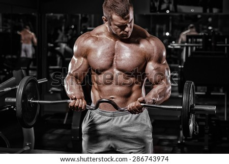 Athlete muscular bodybuilder training biceps with EZ barbell in the gym  - stock photo