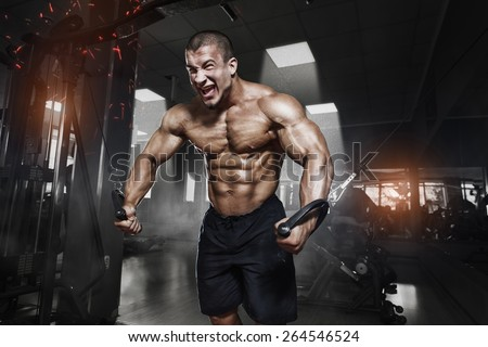 Athlete muscular bodybuilder training on simulator in the gym - stock photo