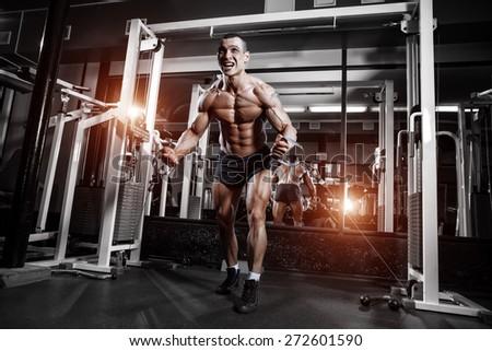 Athlete muscular bodybuilder training on simulator in the gym - stock photo